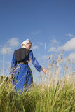 Low angle view of Amish girl walking in a field. A low angle view of an Amish girl walking in a field touching the grass Stock Image