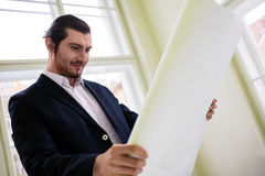 Low angle view of architect holding blueprint Stock Photos