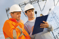 Low angle view of architects discussing over clipboard Royalty Free Stock Images