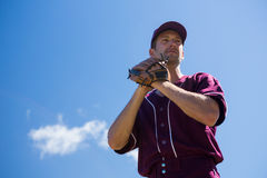 Low angle view of baseball pitcher standing against blue sky. On sunny day Royalty Free Stock Image
