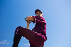 Low angle view of baseball pitcher throwing ball against blue sky Royalty Free Stock Images