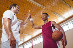 Low angle view of basketball player high fiving with coach. While standing in court Stock Image
