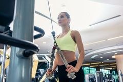 Low-angle view of a beautiful fit woman exercising with cable rope. Low-angle view of a beautiful fit woman with a serious facial expression exercising cable royalty free stock photography