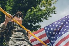 Low angle view of boy in sunglasses pulling himself up on crossbar with american flag. On backdrop royalty free stock photos