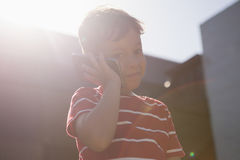 Low angle view of boy talking on mobile phone while standing against sky Royalty Free Stock Image