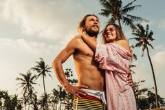 Low angle view of boyfriend and girlfriend. Hugging on beach in bali indonesia stock image