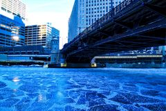 Low-angle view of bridge crossing a frozen Chicago River on a blue, frigid morning in winter. Low-angle view of bridge crossing a frozen Chicago River on a blue stock photography