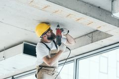 Low angle view of builder in protective googles and hardhat working with drill at construction. Site royalty free stock image