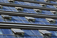 Abstract Windows. Low angle view at a building's curtain wall, with most its windows identically open, creating an interesting diminishing abstract view Royalty Free Stock Images