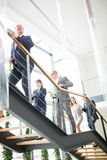 Business Colleagues Climbing Stairs In Modern Office. Low angle view of business colleagues climbing stairs in modern office royalty free stock photo