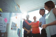 Low angle view of business colleagues discussing over whiteboard at office. During sunny day royalty free stock image