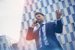 Low angle view of business man gesturing while speaking on mobile phone Royalty Free Stock Photo