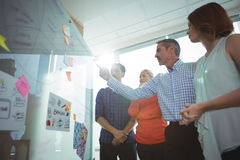 Low angle view of business people discussing over whiteboard at office. During sunny day royalty free stock photo