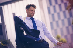 Low angle view of Businessman holding blazer and newspaper Stock Photography