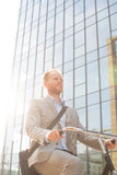 Low angle view of businessman riding bicycle outside office building on sunny day royalty free stock photos