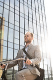 Low angle view of businessman riding bicycle outside office building on sunny day Stock Images