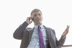 Low angle view of businessman talking on cell phone against sky Royalty Free Stock Photos