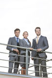 Low angle view of businesspeople standing on terrace against clear sky Royalty Free Stock Photo