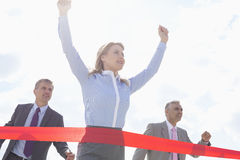 Low angle view of businesswoman crossing finishing line with colleagues in background Stock Image