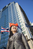 Low angle view of businesswoman in front of a building with Chinese flag in the background Stock Images