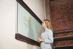 Low angle view of businesswoman standing by glass board in office Royalty Free Stock Photos