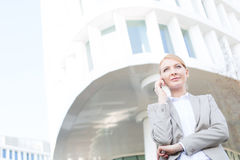 Low angle view of businesswoman using cell phone outside office building Royalty Free Stock Photography