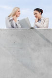 Low angle view of businesswomen looking at laptop while standing on terrace against sky Stock Images