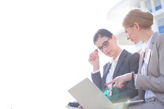 Low angle view of businesswomen using laptop against clear sky Royalty Free Stock Photography