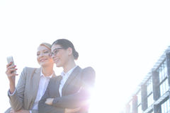 Low angle view of businesswomen using smart phone against clear sky on sunny day Stock Photo