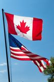 Low angle view of Canadian and American flags, Stock Image