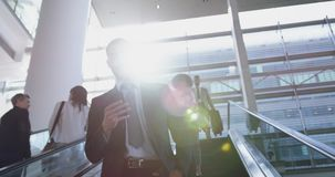 Businessman using mobile phone on escalator in a modern office 4k. Low angle view of Caucasian Businessman using mobile phone on escalator in a modern office. He stock video