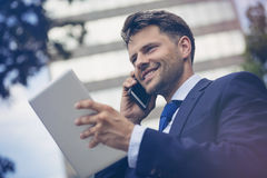 Low angle view of cheerful businessman with mobile and digital tablet Stock Photos