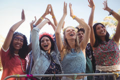 Low angle view of cheerful female fans enjoying music festival Stock Photos