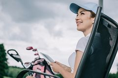 low angle view of cheerful female golf player in cap with tablet