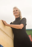 Low angle view of cheerful woman carrying surfboard. While standing against clear sky stock image