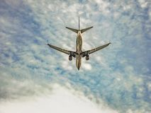 Plane Flying Low Angle View. Low angle view of commercial plane flying at blue sky Stock Image