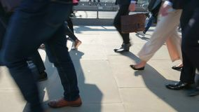 Low angle view of commuters legs. Low angle view pan of commuters at rush hour on london bridge london themes of routines on the move commuters rush hour stock footage