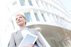 Low angle view of confident businesswoman holding digital tablet outside office building Stock Images