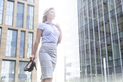 Low angle view of confident businesswoman holding high heels while standing outside office buildings Stock Image
