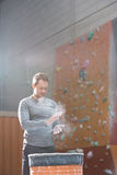 Low angle view of confident man dusting powder by climbing wall in crossfit gym Stock Photography