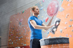 Low angle view of confident man dusting powder by climbing wall in crossfit gym Royalty Free Stock Photo