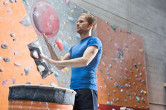 Low angle view of confident man dusting powder by climbing wall in crossfit gym Royalty Free Stock Photography