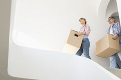 Low angle view of couple with boxes moving into new house Stock Image
