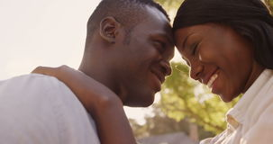 Low angle view of couple embracing. In a park stock video footage