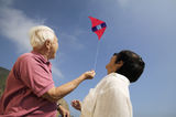 Low Angle View Of A Couple Flying Kite Royalty Free Stock Photo