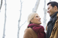 Low angle view of couple looking at each other in park during autumn Stock Photo