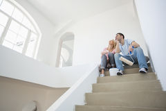 Low angle view of couple with painting tools sitting on steps in new house Royalty Free Stock Photo