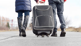 Low angle view of a couple pulling a suitcase Royalty Free Stock Photos