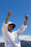 Low angle view of cricket umpire signalling six runs against blue sky. During match on sunny day Royalty Free Stock Image