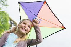 Low angle view of a cute girl with a kite Royalty Free Stock Image